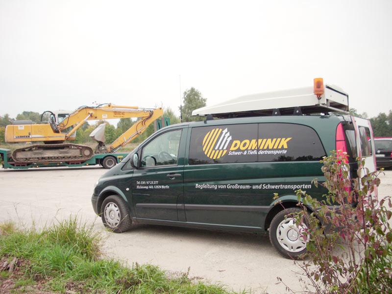 Firmenwagen Transporte Dominik vor Baumaschine