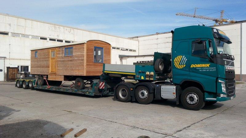 Transport eines Bauwagens aus Holz mit Tieflader